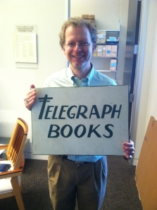 John Pollack proudly holding an artifact of the Telegraph Books collection: a hand-painted sign!